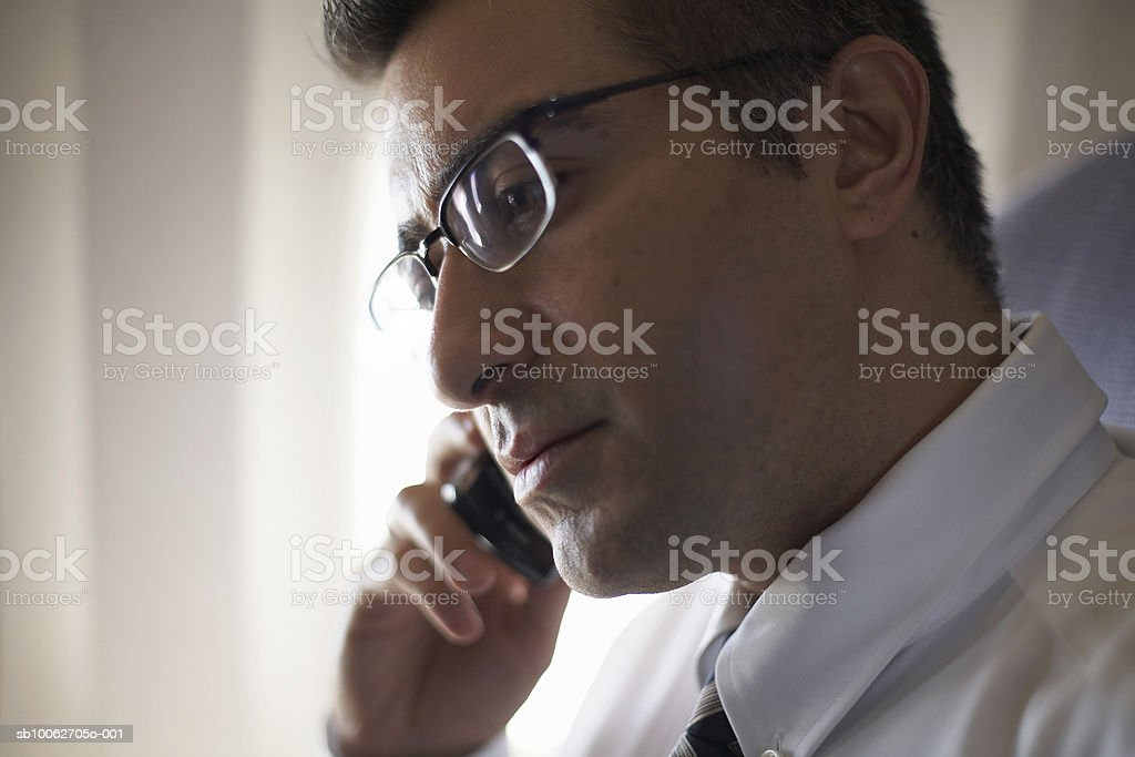 Mid adult business man wearing spectacles using mobile phone, sitting in airplane royalty-free stock photo