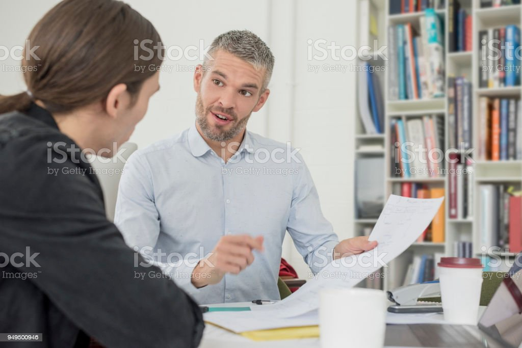 Mid adult business manager with grey beard talking to younger male colleague stock photo