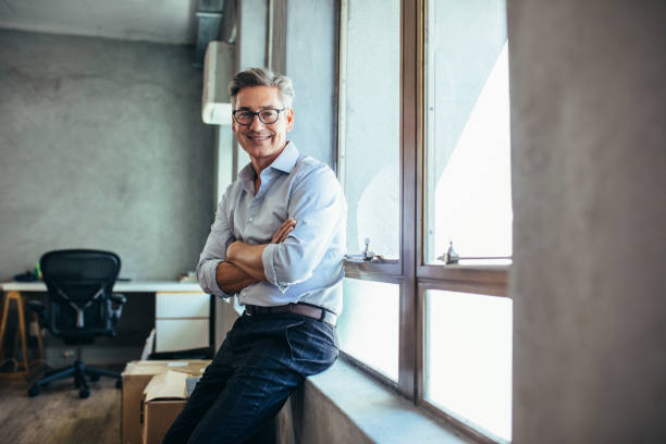 Mid adult businessman at his office Smiling businessman looking at camera as he stands by a window sill with arms crossed. Mid adult businessman at his office. jacoblund stock pictures, royalty-free photos & images
