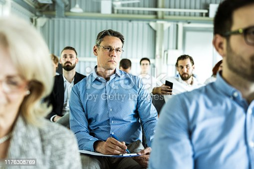 istock Mid adult businessman attending a training class in a board room. 1176308769