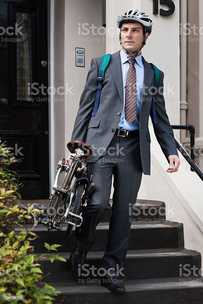 Mid adult businessman carrying folding bicycle down steps stock photo