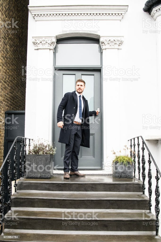 Mid adult  businessman closing front door and standing outside house stock photo