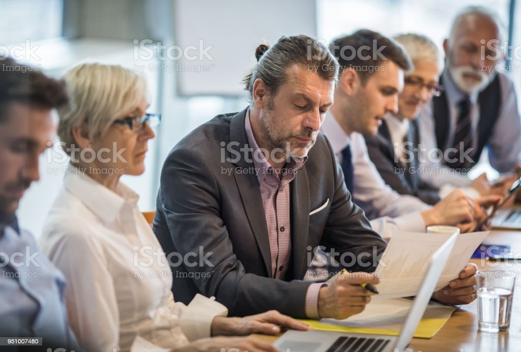 Mid adult businessman going through paperwork on a meeting with his colleagues. stock photo