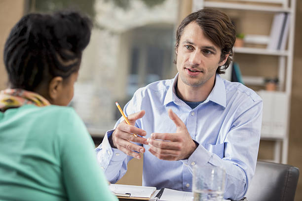 mid adult businessman interviews potential employee - psychiatrist stock photos and pictures