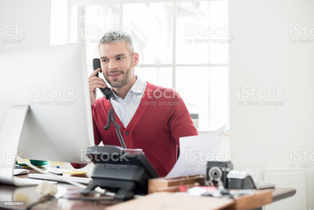 Mid adult businessman on phone in office looking at computer monitor stock photo