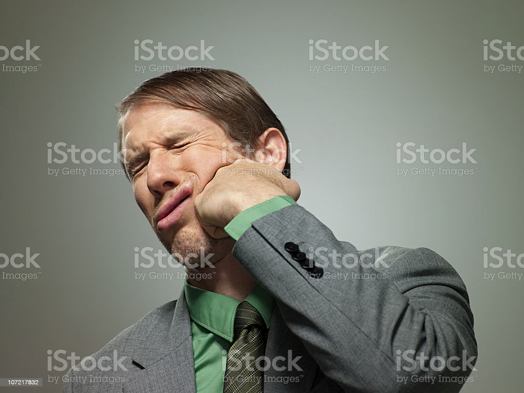 Mid adult businessman punching himself in face, portrait stock photo