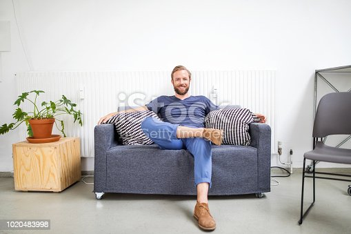 Portrait of mid adult businessman sitting on sofa. Smiling man in casuals relaxing in office.
