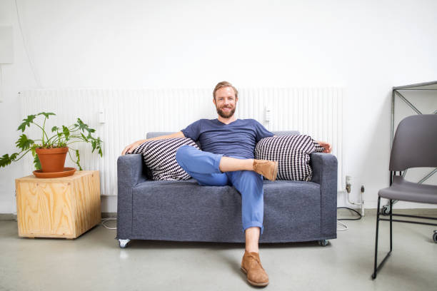mid adult businessman relaxing on sofa - guy sofa foto e immagini stock
