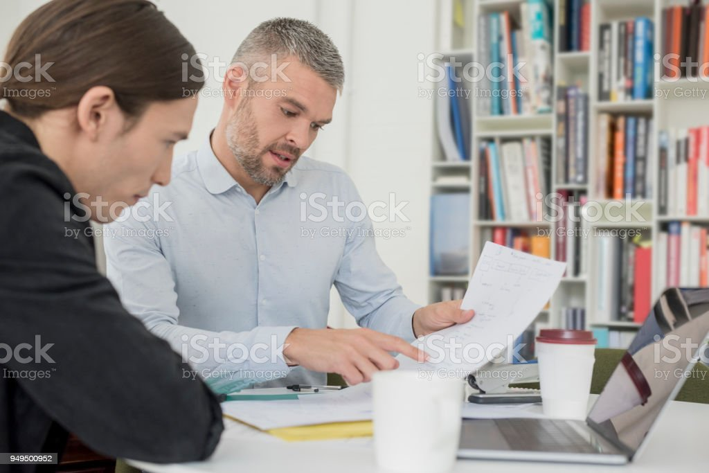Mid adult businessman showing young male colleague document and explaining stock photo