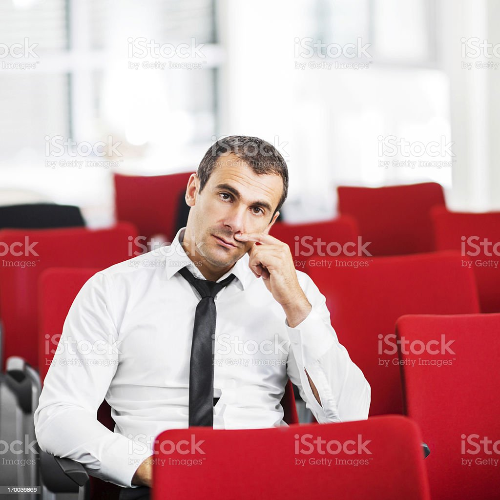 Mid adult businessman sitting alone on a seminar. stock photo
