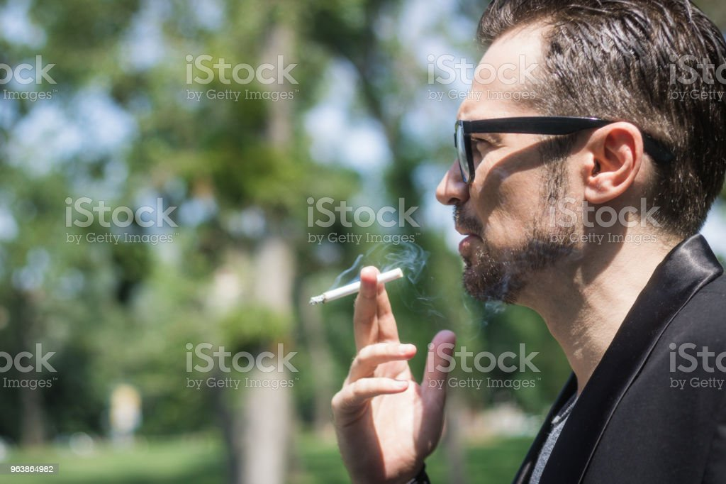 Mid adult businessman smoking cigarette outdoors. - Royalty-free Addiction Stock Photo