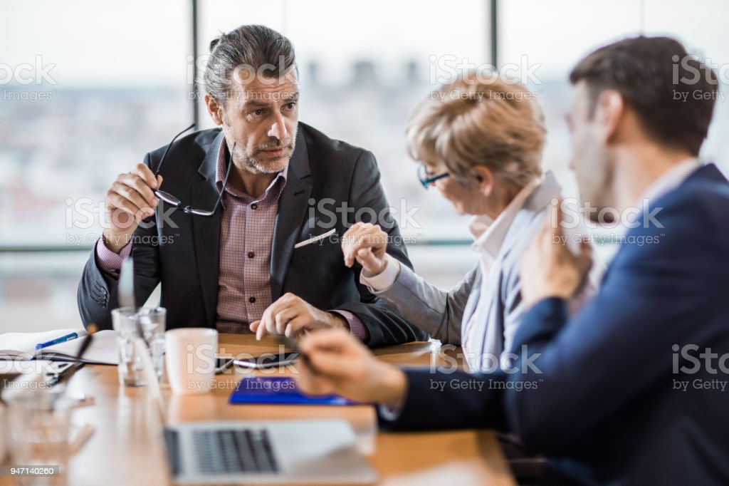Mid adult businessman talking to his colleagues on a meeting. stock photo