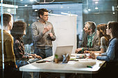 istock Mid adult businessman talking to his colleagues on presentation in the office. 1127305026