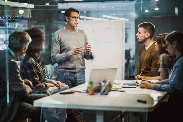 medio hombre de negocios adulto hablando con sus colegas en la presentación en la oficina. - ingeniero fotografías e imágenes de stock