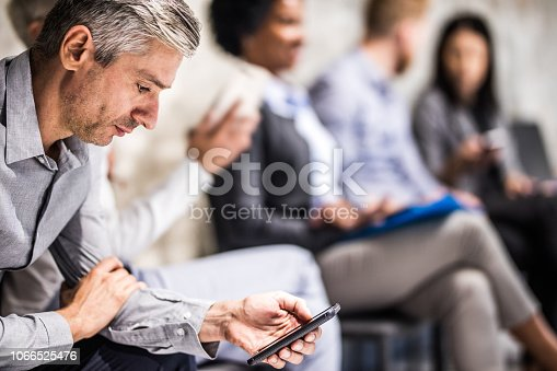 Mid adult businessman text messaging on smart phone while waiting for a job interview. There are people in the background.