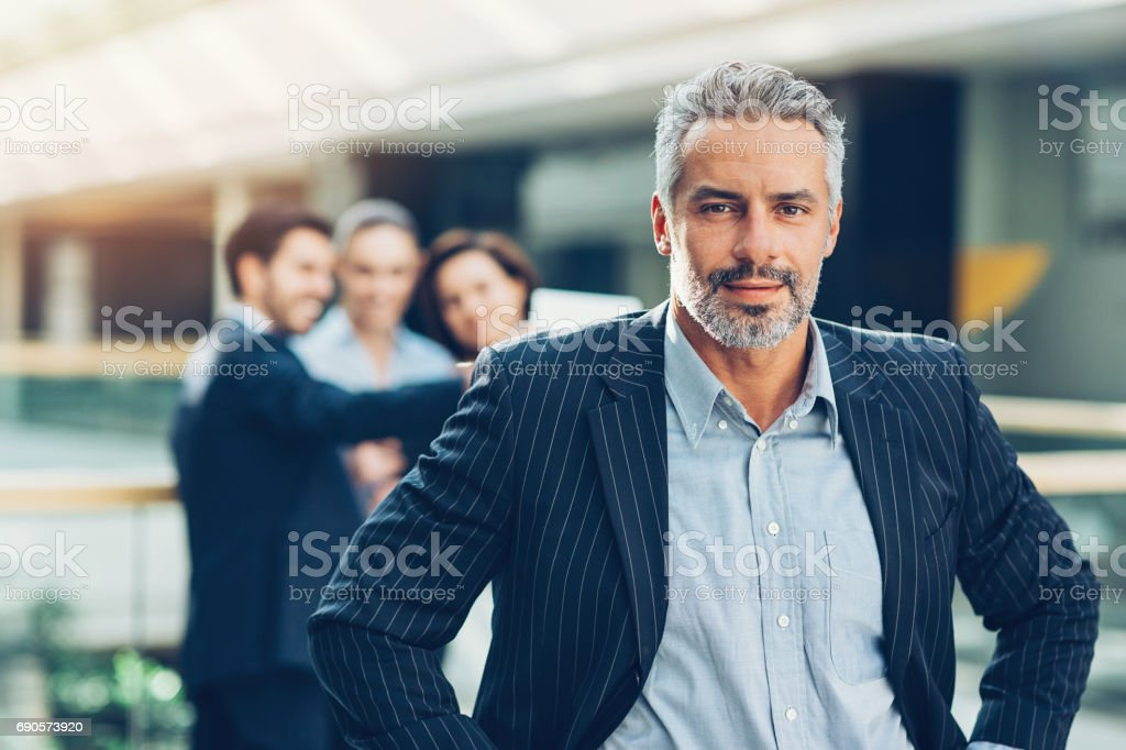 Mid adult businessman with his team behind stock photo