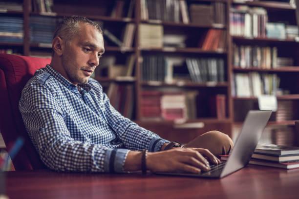 mid adult businessman working on laptop at home library. - professore di scuola superiore foto e immagini stock