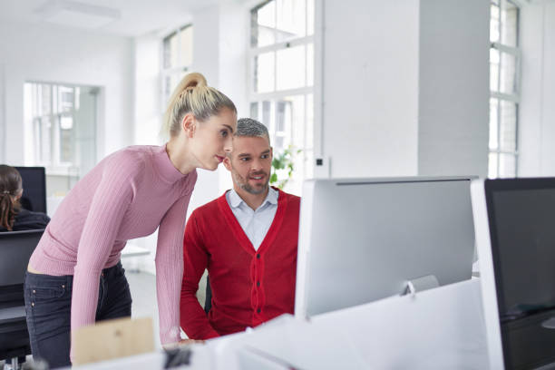Mid adult businessman working together with his colleague in the office stock photo