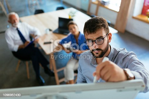 Mid adult businessman writing a business plan on whiteboard during a meeting at conference room