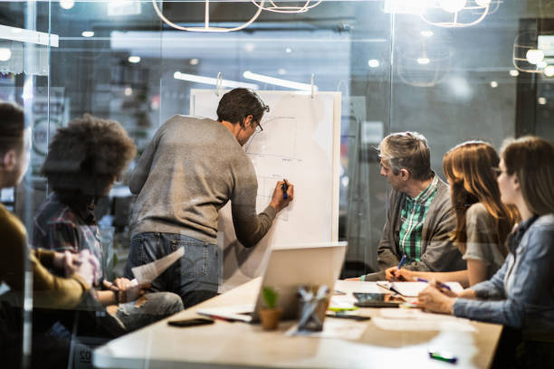 mittlere erwachsene geschäftsmann schreiben pläne während der präsentation mit seinen kollegen im büro. - geschäftsstrategie stock-fotos und bilder