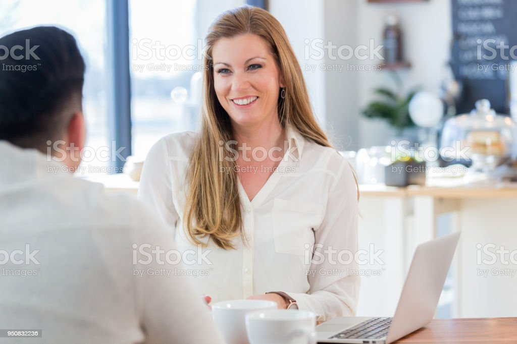 Mid adult businesswoman enjoys coffee shop discussion stock photo