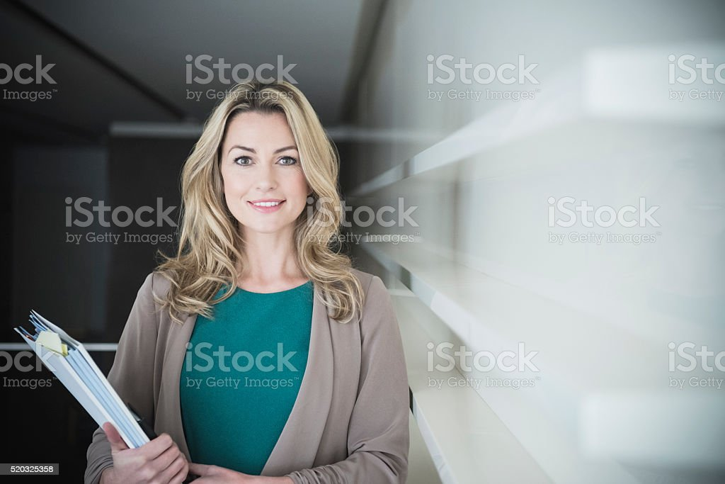Mid adult businesswoman holding file at work stock photo
