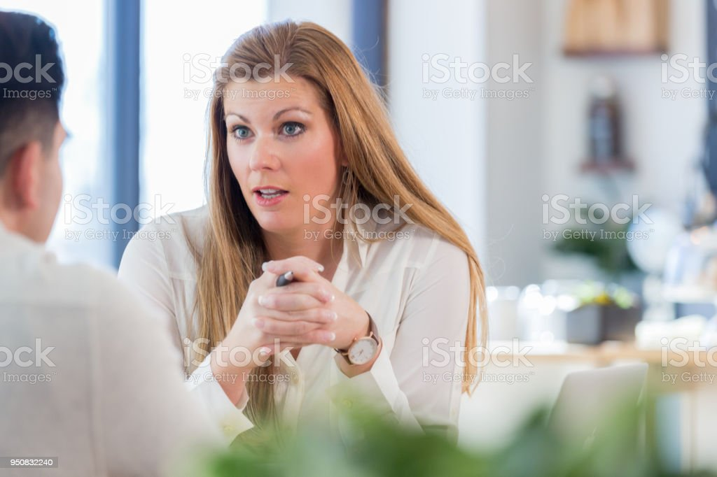 Mid adult businesswoman in intense discussion in coffee shop stock photo