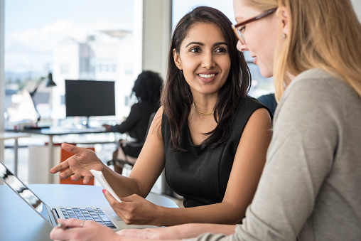 istock Mid adult businesswoman listening to female colleague in office 635850472