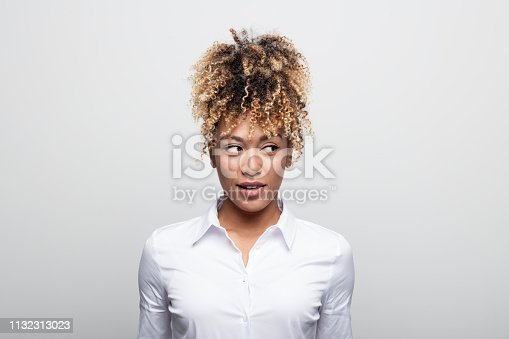Mid adult businesswoman looking sideways. Beautiful female manager is having curly blond hair. She is against white background.