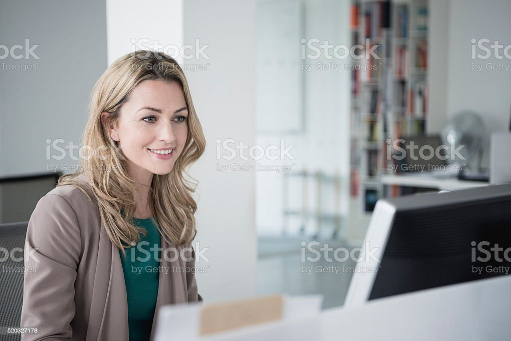 Mid adult businesswoman using desktop computer, smiling stock photo