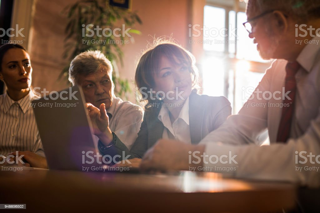 Mid adult businesswoman using laptop and communicating with her coworkers. stock photo