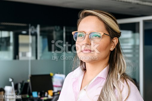Portrait of woman in her 30s in modern office, looking away, contented expression, contemplation