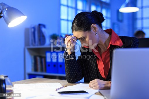 istock Mid adult businesswoman working late, headache 1067014382