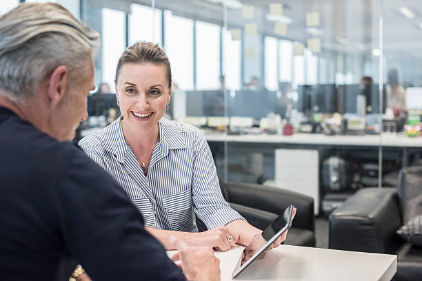 Mid adult busineswoman using tablet with mature man, smiling stock photo