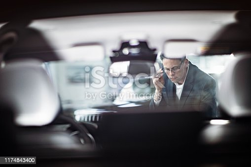 Mid adult salesperson working in a car showroom. The view is through glass.
