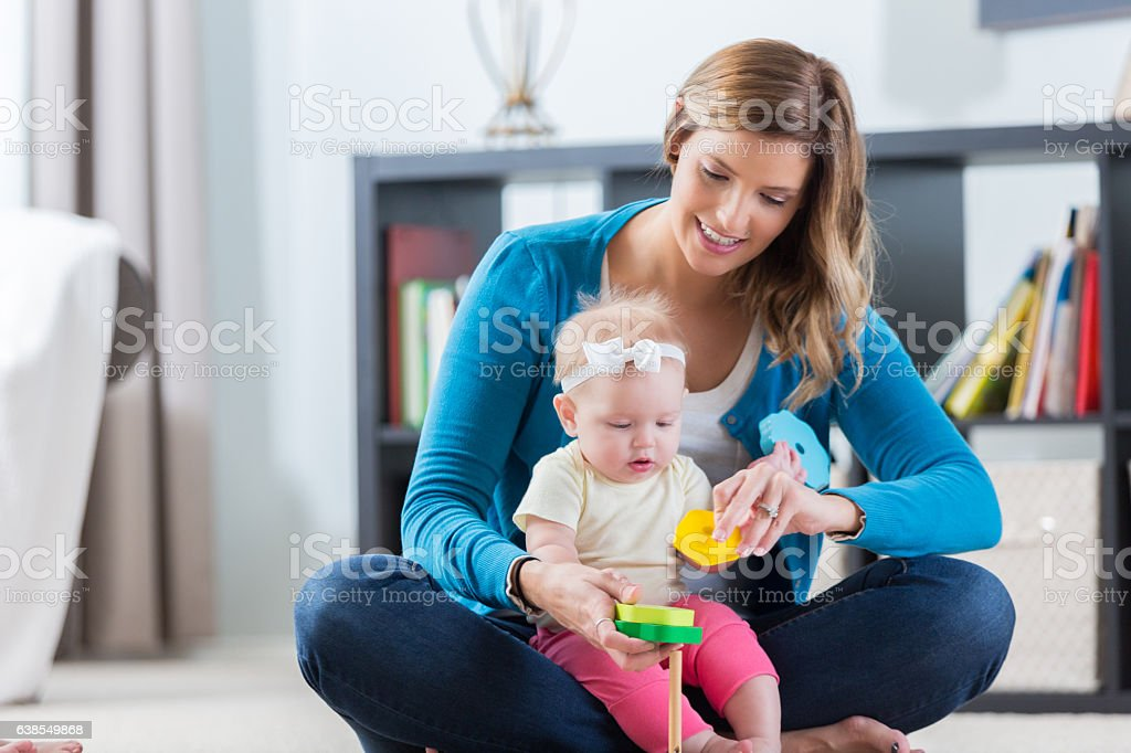 Mid adult Caucasian nanny plays with baby stock photo