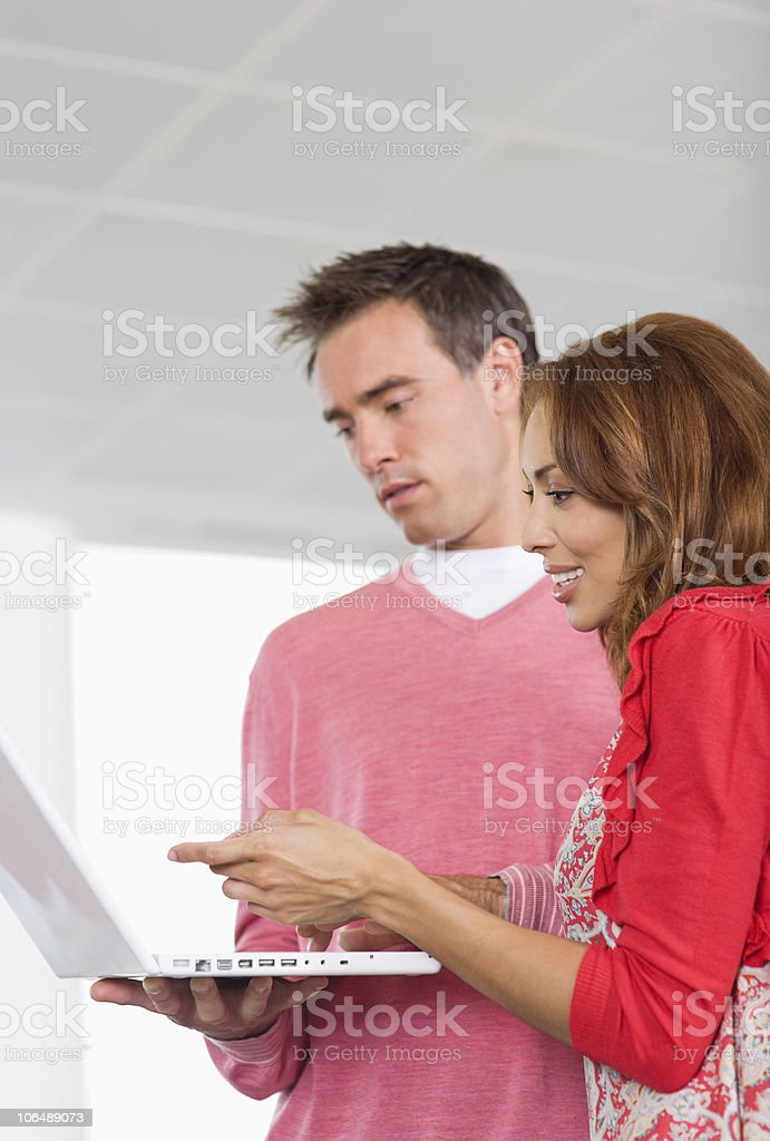 Mid adult colleagues using a laptop royalty-free stock photo