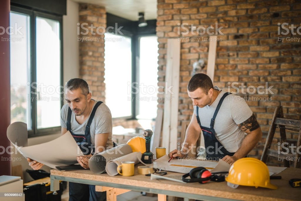 Mid adult construction workers going through housing plan during renovation process. stock photo