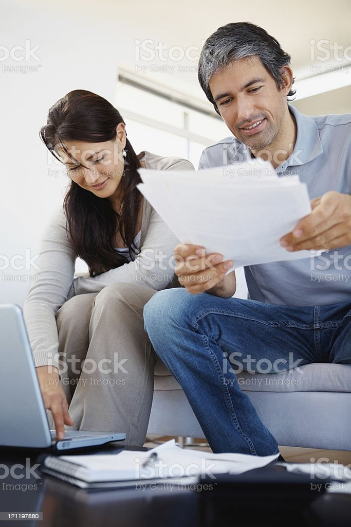 Mid adult couple checking out financial documents Mid adult couple checking out financial documents at home 30-39 Years Stock Photo