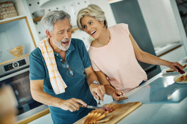 Mid adult couple cooking lunch together. stock photo