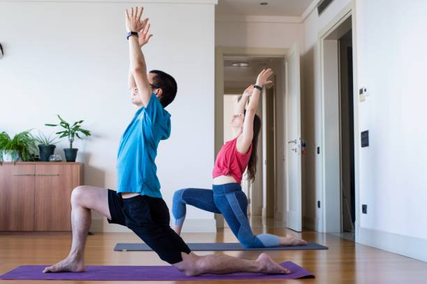 Mid adult couple doing yoga at home stock photo