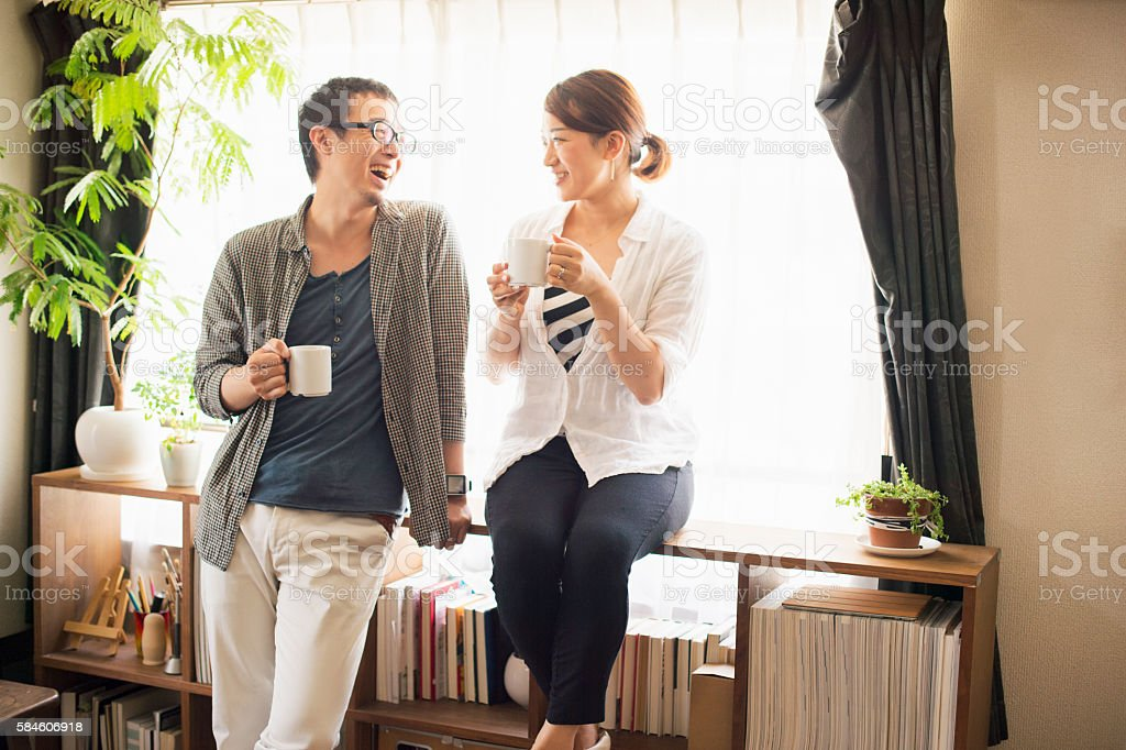 Mid adult couple drinking coffee at home stock photo