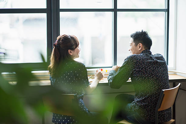 mid adult couple enjoying lunch in cafe. - カフェ ストックフォトと画像