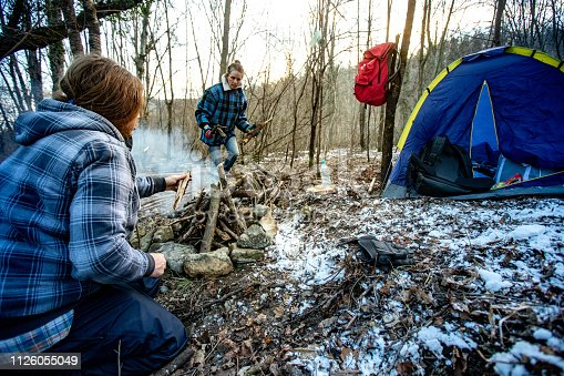 Mid Adult Couple Firing Up Campfire While Camping in Winter.