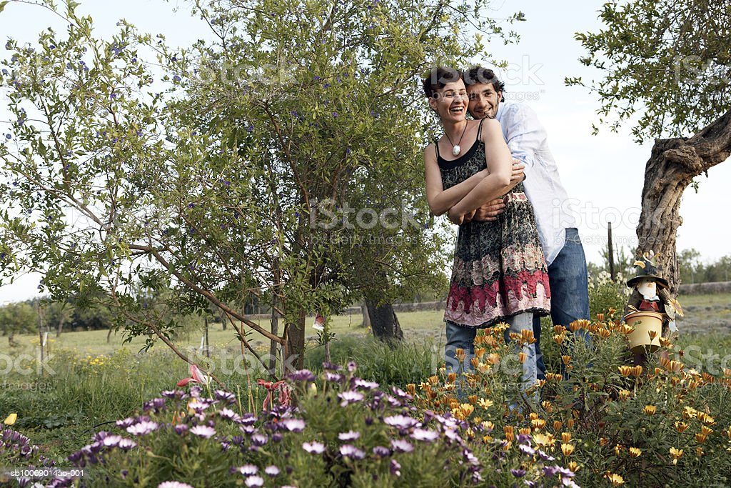 Mid adult couple hugging in flower garden royalty-free stock photo