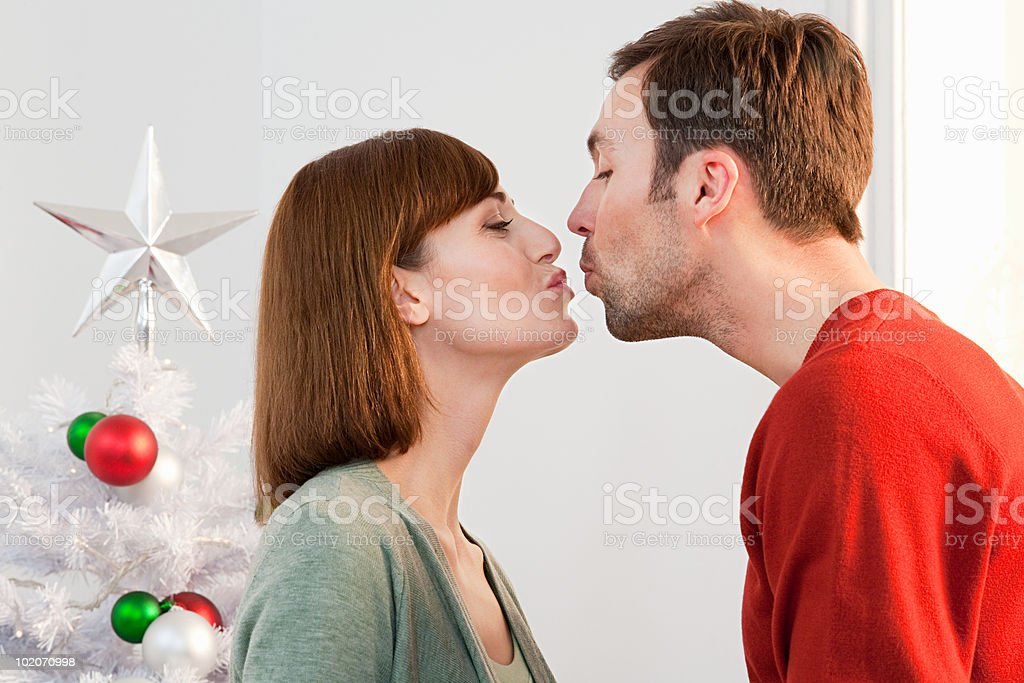 Mid adult couple kissing at Christmas time royalty-free stock photo