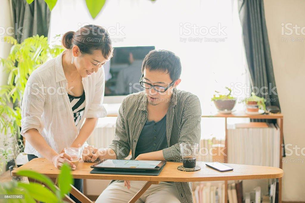 Mid adult couple looking at a digital tablet ストックフォト