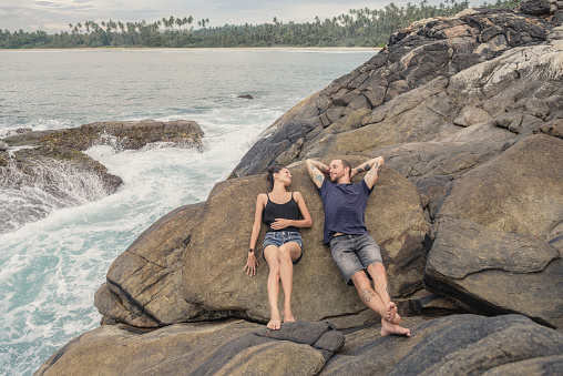 Mid adult couple lying on rocks relaxing
