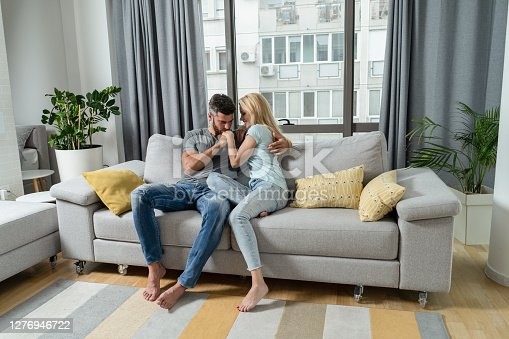 Romantic young couple sitting together on sofa in the living room and embracing.