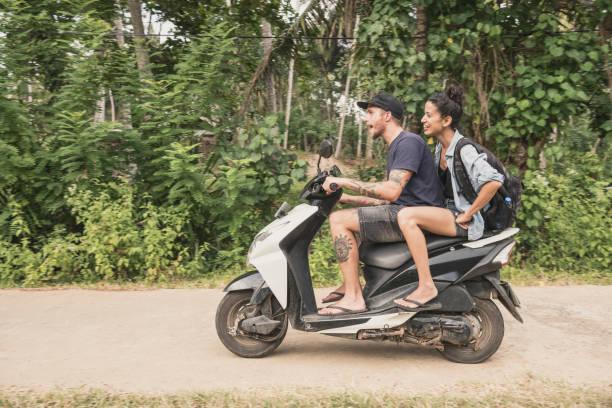 couple adulte mid, équitation cyclomoteur à travers forêt, vue latérale - moped photos et images de collection